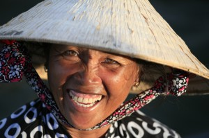 Boat woman wearing palm-leaf conical hat, Can Tho floating market, Delta of Mekong, Vietnam.